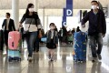 Travellers wearing face masks walk through Hong Kong International Airport on Wednesday as the coronavirus spreads globally. Photo: Bloomberg