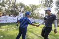 Jazz Janewattananond, of Thailand, shakes hands with a young golfer taking part in the Beat the Pro competition during the Hong Kong Open. Photo: Dickson Lee
