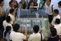 China visitors inspect a model of a public housing estate to be launched in Singapore. Photo: Reuters