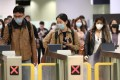 People wearing masks pass through exit gates in the arrival hall of West Kowloon railway station on January 22. Photo: Bloomberg