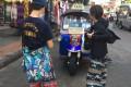 Tourists wear 'elephant pants' in front of a tuk-tuk in Bangkok. Photo: DPA