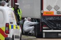 British Police forensics officers work on the truck, found to contain the bodies of 39 people. Photo: AFP