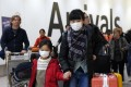 Passengers wear protective masks as they arrive at London's Heathrow Airport. The first confirmed cases of the Chinese coronavirus were reported in Europe on Friday. Photo: EPA-EFE
