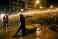 An anti-government protester uses a sling to hurl stones at riot policemen during clashes in Beirut. Photo: DPA