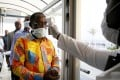 An Ivorian health worker checks the temperature of Ivorian Minister of Health and Public Hygiene Eugene Aka Aoule (left) as the country steps up screening for coronavirus at Felix Houphouet-Boigny Airport in Abidjan on Sunday. Photo: EPA-EFE