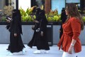 A Saudi woman wearing Western clothes walks past other women wearing conservative clothing in the capital, Riyadh. Photo: AFP