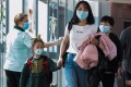 A health officer screens arriving passengers from China at Changi International airport in Singapore, where a fifth coronavirus case has been confirmed. Photo: AFP