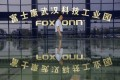 A man walks past the logo of Foxconn Technology Group at a factory in Wuhan, Hubei province. Photo: Reuters
