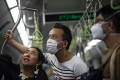 A man wearing a protective mask rides the train in Singapore. Photo: EPA