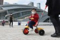 A child with a face mask plays on his bike outside the West Kowloon terminus of the high-speed railway to mainland China. Services have been suspended because of the Wuhan coronavirus outbreak. Photo: Winson Wong