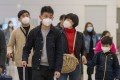 Masks on as passengers make their way through the arrival hall of the West Kowloon high-speed rail station on January 28. Hong Kong has announced the shutdown of two railway services and the suspension of new visas to individual mainland tourists. Photo: Bloomberg