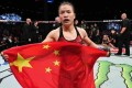 Zhang Weili celebrates with the Chinese flag after winning the UFC strawweight title in Shenzhen. Photo: Brandon Magnus/Zuffa LLC
