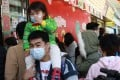 Families are struggling to get hold of surgical masks, leading to long queues outside shops. Photo: May Tse