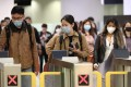 People wearing face masks pass through exit gates in the arrivals hall inside West Kowloon Station in Hong Kong. Photo: Bloomberg