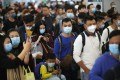Travellers wearing masks queue at the West Kowloon high-speed railway station, in Hong Kong, on January 23. Photo: Winson Wong