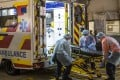 Ambulance workers in protective gear load a stretcher at Queen Mary Hospital in Hong Kong on Wednesday. Photo: Bloomberg