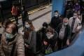 Mask-wearing passengers board an escalator at Kowloon Tong station on January 30. Photo: Bloomberg