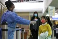 A Kenyan health worker screens a young passenger upon her arrival from China at Jomo Kenyatta International Airport in Nairobi on Wednesday. Photo: EPA-EFE