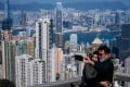 A couple take a selfie sans face masks, with Hong Kong's famous skyline in the backdrop. Photo: AFP