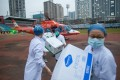 Staff of Concorde hospital transfer medical supplies from a helicopter in Wuhan. Photo: EPA-EFE