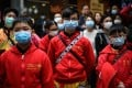 Members of a Chinese lion dance team wear face masks during a performance in Mong Kok, Hong Kong, on February 1, the seventh day of the Lunar New Year. There is no need to panic, but the coronavirus can't be checked unless ordinary residents do their part to minimise person-to-person contact and observe good hygiene. Photo: AFP