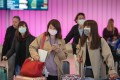 Passengers wear face masks to protect against the novel coronavirus, as they arrive at Los Angeles International Airport on January 22. Photo: AFP