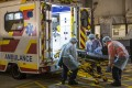 Medical officers in protective gear load a stretcher onto an ambulance outside Queen Mary Hospital in Hong Kong on January 29, 2020. Photo: Bloomberg