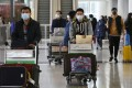 Masked travellers arrive at the Hong Kong International Airport amid the deadly coronavirus outbreak. Photo: Jonathan Wong