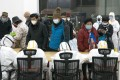 Medical workers in Wuhan help patients infected with the novel coronavirus check in at a makeshift hospital, converted from an exhibition centre, on Wednesday. Photo: Xinhua
