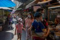 Tourists walk through Bangkok's Chinatown. Thailand's central bank has cut its benchmark interest rate to help the economy weather the virus outbreak in China that has devastated its tourism sector. Photo: AP