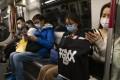 Passengers wearing medical masks ride an MTR train in Hong Kong. Photo: Sun Yeung