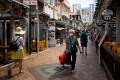 A shopper wearing a protective mask walks past stores in the Chinatown area of Singapore on February 10. Singapore hasraisedits disease response level to the same grade used during the Sars epidemic. Photo: Bloomberg