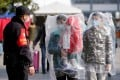 Passengers wearing masks and covered with plastic bags walk outside the Shanghai railway station in Shanghai, China, as the country is hit by an outbreak of a new coronavirus, February 9, 2020. Photo: Reuters