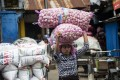 An Indonesian woman carries bags of garlic at a market in Surabaya. Photo: AFP