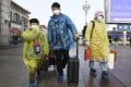 Passengers wear masks and raincoats at Beijing Station on Monday to protect themselves from the coronavirus. Photo: Kyodo