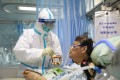 A nurse in a protective suit feeds a coronavirus patient in an isolated ward in Wuhan. Photo: Reuters