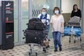 Passengers wear protective face masks at Brisbane International Airport. Photo: EPA