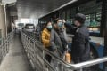 An official checks the temperature of passengers at a bus terminal in Shanghai. Photo: Bloomberg