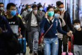 Passengers wear face masks as they arrive from Shenzhen at Lo Wu MTR station, hours before the closing of the Lo Wu border crossing in Hong Kong on February 3. Photo: AFP