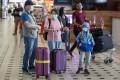 Passengers wearing face masks arrive at Brisbane International Airport. Photo: AFP