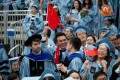 Graduates wave Chinese flags during a commencement ceremony at Columbia University in New York on May 16, 2018. Photo: Xinhua