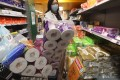 A shopper with a cart brimming with toilet rolls. Photo: Nora Tam