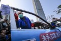 Secretary for Transport and Housing Frank Chan Fan helps disinfect a taxi at February 17 event to promote protective measures during the coronavirus outbreak. Photo: Felix Wong