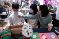 Students sit behind a stall selling beauty face masks at a democracy-themed Lunar New Year fair on January 28. Classes were suspended after the new year break in an effort to contain the spread of the coronavirus, and the school closures have since been extended to March 16. Photo: EPA-EFE