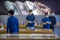 Employees wear face masks as they stand in a reopened Apple Store in Beijing on Friday. Photo: AP