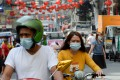 Motorists wearing face masks making their way along a street in Manila's Chinatown district of Binondo. Photo: AFP