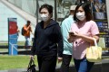 Two women wearing protective face masks, amid concerns over the spread of the COVID-19 coronavirus, walk on the street in Singapore on February 14, 2020. Photo: AFP