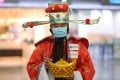 An MTR employee dressed as the god of wealth wears a mask at West Kowloon Station to avoid contracting the Covid-19 disease. The region's wealthy investors have been going about their business as usual even the outbreak began to spread. Photo: Winson Wong