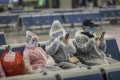 A family wearing masks and makeshift protection gear wait for their train at the Hongqiao high-speed railway station in Shanghai on February 11. More than 75,000 cases of coronavirus infection have so far been reported with over 2,000 deaths. Photo: Bloomberg