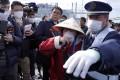 A passenger is surrounded as she disembarks the Diamond Princess cruise ship in Yokohama, Japan. Photo: EPA